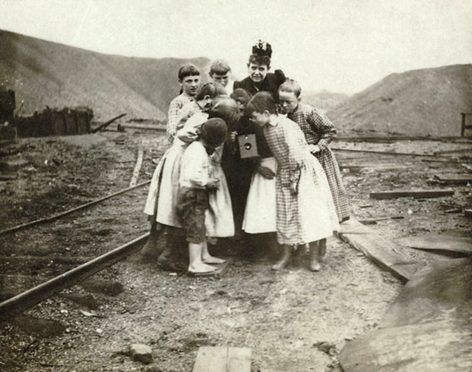 Frances Benjamin Johnston holding camera while excited children crowd around