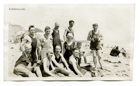 Vintage snapshot of 1920s group at the beach, including camera