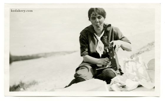 Beach woman holding fold-out camera, circa 1910