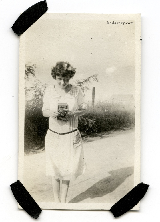 Vintage snapshot of a girl holding an old camera